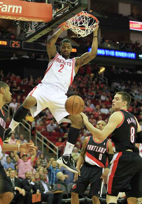 Houston's Marcus Morris (2) hangs from the basket after scoring against Portland's Luke Babbitt (8) during the first half of the home opener NBA game at Toyota Center, Saturday, Nov. 3, 2012, in Houston.   ( Karen Warren / Houston Chronicle ) Photo: Karen Warren, Staff / © 2012  Houston Chronicle