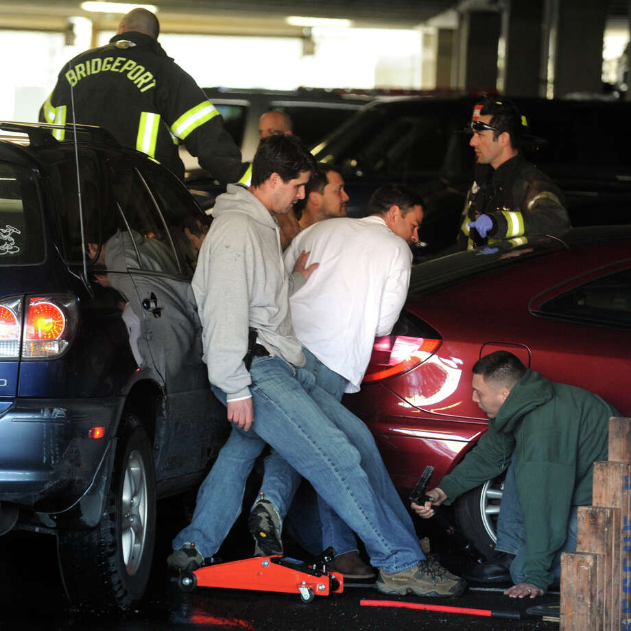 Volunteers help Bridgeport firefighters as they work to free a woman pinned between two cars in the parking gararge at 1000 Lafayette Blvd., in Bridgeport, Conn., Feb. 13th, 2013. Photo: Ned Gerard / Connecticut Post