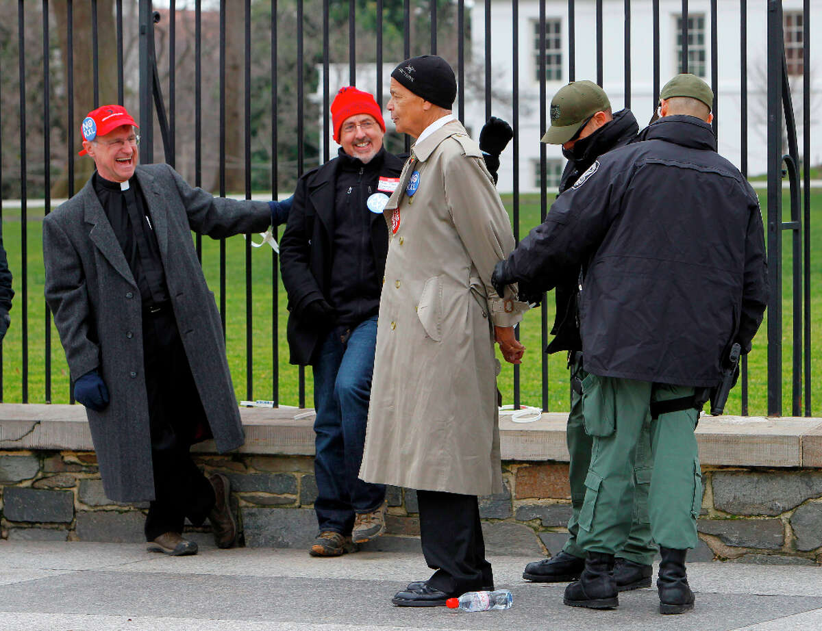 Civil rights leader Julian Bond is arrested outside the White House in Washington, Wednesday, Feb. 13, 2013, as prominent environmental leaders tied themselves to the White House gate to protest the Keystone XL oil pipeline.