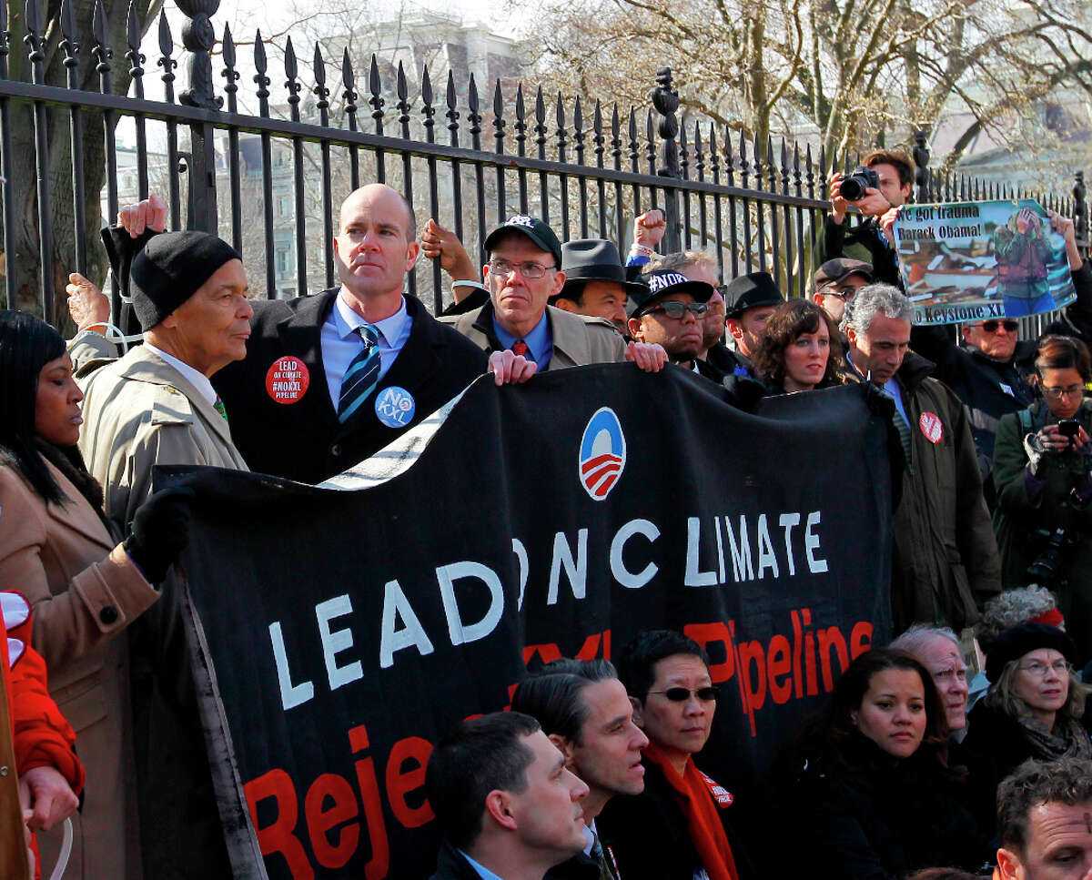 Civil rights protester Julian Bond, left, and Sierra Club Executive Director Michael Brune, second from left, gather with activists in front of the White House in Washington, Wednesday, Feb. 13, 2013, as prominent environmental leaders tied themselves to the White House gate to protest the Keystone XL oil pipeline.