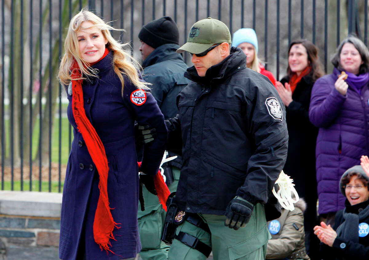 Actress Daryl Hannah is arrested outside the White House in Washington, Wednesday, Feb. 13, 2013, as prominent environmental leaders tied themselves to the White House gate to protest the Keystone XL oil pipeline.