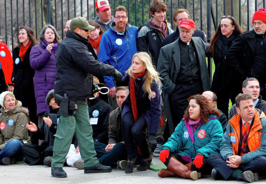 Actress Daryl Hannah is helped up before she is arrested outside the White House in Washington, Wednesday, Feb. 13, 2013, as prominent environmental leaders tied themselves to the White House gate to protest the Keystone XL oil pipeline. Photo: Ann Heisenfelt, Associated Press / FR13069 AP