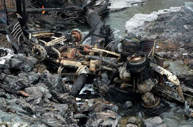 The charred and melted remains of a gasoline tanker truck's tractor and cab, lies at the bottom of a hill below Route 7 Feb. 13, 2013 after is left the road and exploded in Hoosick, N.Y.   The driver received burns and was ultimately transported to the Westchester Burn Center.   (Skip Dickstein/Times Union) Photo: SKIP DICKSTEIN