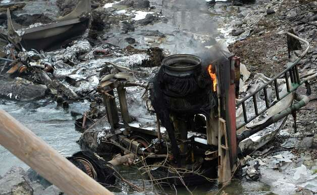 The melted remains of a gasoline tanker truck looking from the rear to the front, lies at the bottom of a hill below Route 7 Feb. 13, 2013 after is left the road and exploded in Hoosick, N.Y.   The driver received burns and was ultimately transported to the Westchester Burn Center.   (Skip Dickstein/Times Union) Photo: SKIP DICKSTEIN