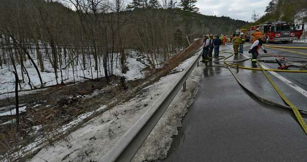 Firefighters, DEC and law enforcement members start the investigation as to how a gasoline tanker wound up at  the bottom of a hill below Route 7 Feb. 13, 2013 after is left the road in Hoosick, N.Y.   The driver received burns and was ultimately transported to the Westchester Burn Center.   (Skip Dickstein/Times Union) Photo: SKIP DICKSTEIN