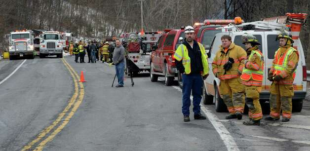 Firefighters, ENCON and law enforcement members start the investigation as to how a gasoline tanker wound up at  the bottom of a hill below Route 7 Feb. 13, 2013 after is left the road in Hoosick, N.Y.   The driver received burns and was ultimately transported to the Westchester Burn Center.   (Skip Dickstein/Times Union) Photo: SKIP DICKSTEIN