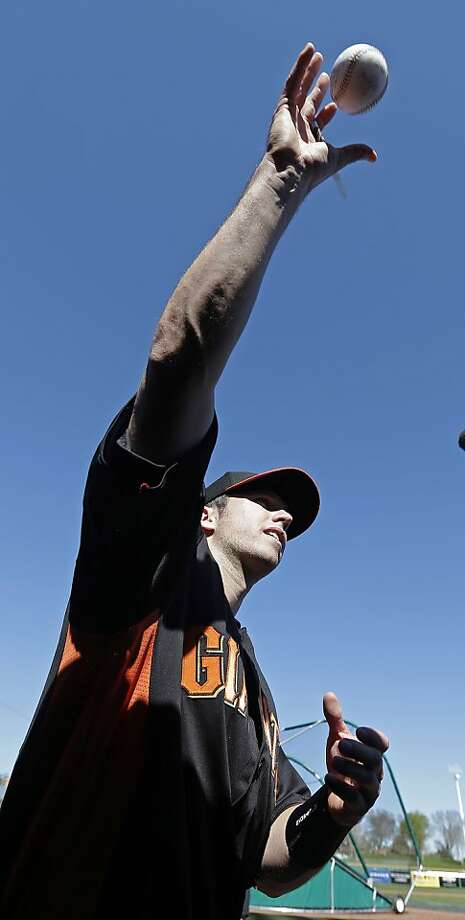 San Francisco Giants' Buster Posey tosses a baseball back to a fan after autographing it following a spring training baseball workout Wednesday, Feb. 13, 2013, in Scottsdale, Ariz. (AP Photo/Darron Cummings) Photo: Darron Cummings, Associated Press