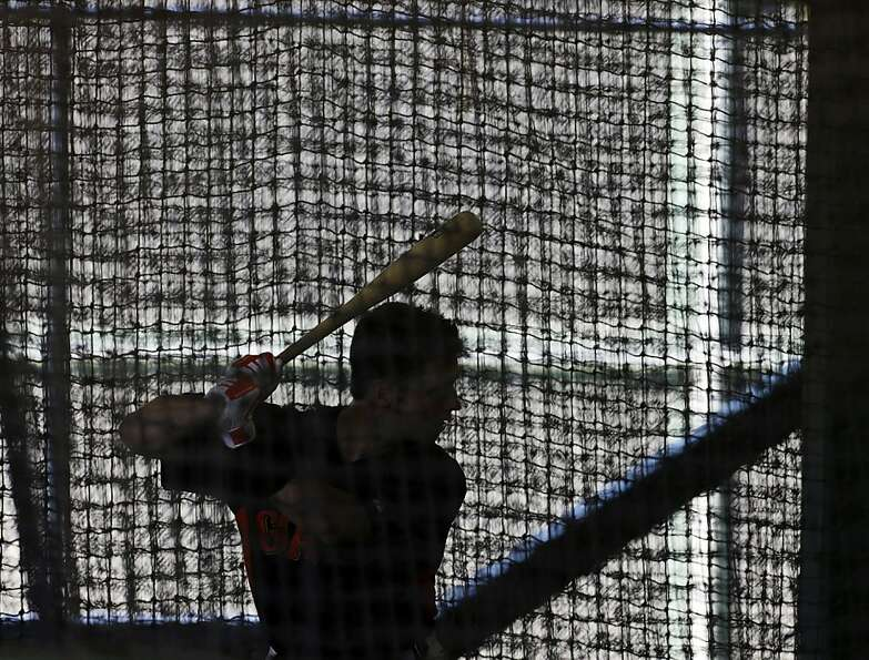 San Francisco Giants' Buster Posey hits in a batting cage during a spring training baseball workout