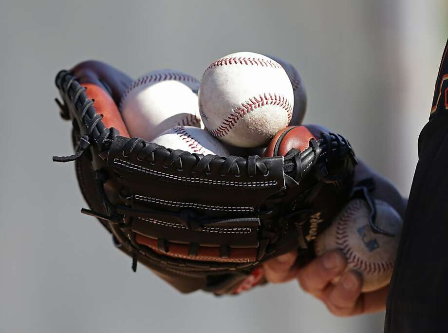 A San Francisco Giants coach holds a catchers mitt full of baseballs during a spring training baseball workout Wednesday, Feb. 13, 2013, in Scottsdale, Ariz. (AP Photo/Darron Cummings) Photo: Darron Cummings, Associated Press