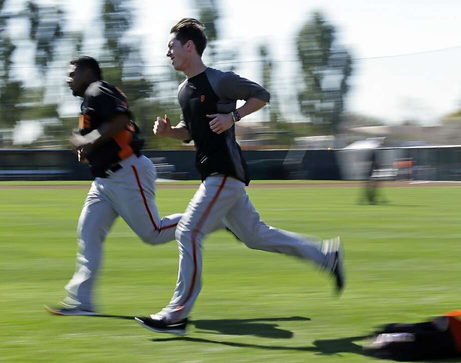 In this image taken with a slow shutter speed, San Francisco Giants' Tim Lincecum, right, and Jean Machi run during a spring training baseball workout Wednesday, Feb. 13, 2013, in Scottsdale, Ariz. (AP Photo/Darron Cummings) Photo: Darron Cummings, Associated Press