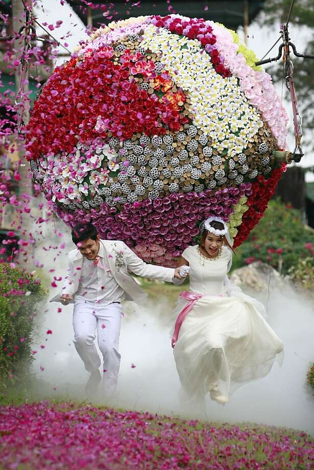 Prasit Rangsitwong, left, and Varutton Rangsitwong run away from a giant flower ball as a part of an adventure-themed wedding ceremony in Prachinburi province, Thailand, Wednesday, Feb. 13, 2013, on the eve of Valentine's Day. (AP Photo/Wason Wanichakorn) Photo: Wason Wanichakorn, Associated Press