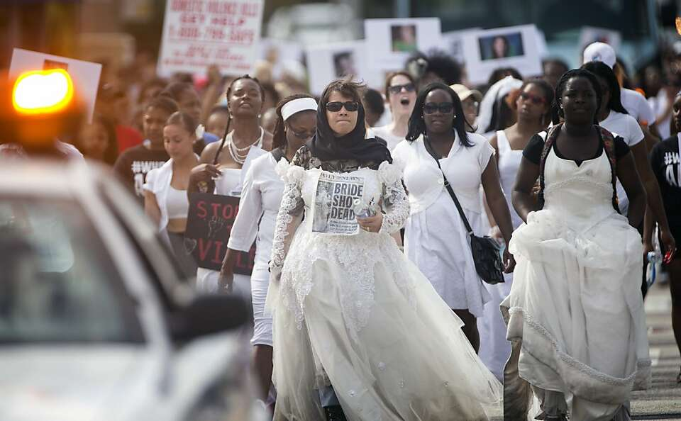Josie Asaton, walking behind a police car and dressed in a wedding dress, leads a group of students