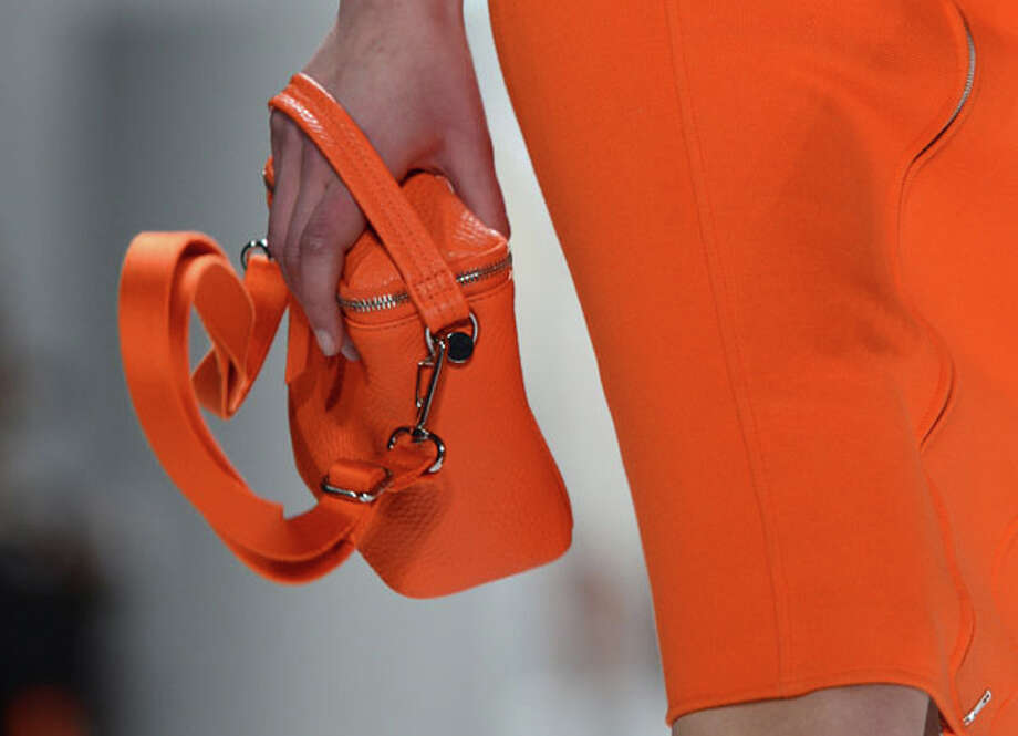 Matching purse in tangerine orange. Lacoste Fall 2013. Photo: STAN HONDA, AP/Getty / AFP