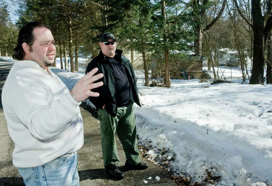 Steve Merkel stands on Cedar Knolls Drive in New Milford, next to the boarder of his property in the background and the proposed Walmart store location, and discusses the area to be clear-cut for the store. Douglas Skelly, president of Cedar Knolls Homeowners Association, listens. Wednesday, Feb. 13, 2013 Photo: Scott Mullin / The News-Times Freelance