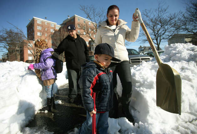 From left; Lilian Ortiz, 7, Miguel Villafane, Giomar Ortiz, 4, and Maraliz Ortiz head back inside after unsuccessfully trying to exit the parking lot at the Charles F. Greene Homes housing project in Bridgeport on Wednesday, February 13, 2013. Residents are frustrated about the lack of snow removal at both the complex and adjacent Highland Avenue. Photo: Brian A. Pounds / Connecticut Post