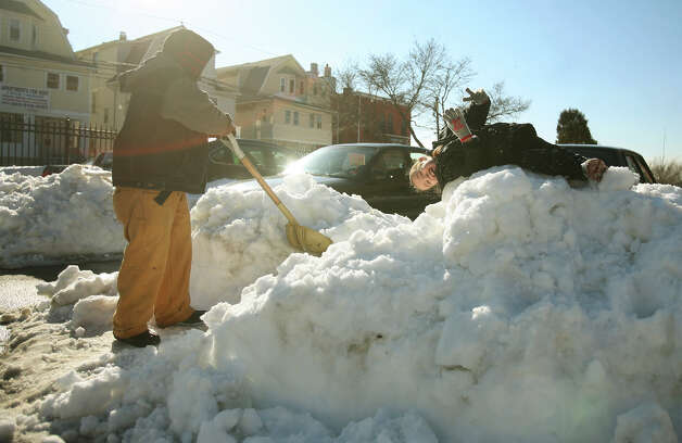 Umberto Figueroa, left, shovels out his car as Anthony Crespo, 5, plays atop a snow pile in the parking lot of Charles F. Greene Homes housing project in Bridgeport, Conn. on Wednesday, February 13, 2013. Residents are frustrated with the lack of snow removal both at the complex, and on adjacent Highland Avenue. Photo: Brian A. Pounds / Connecticut Post
