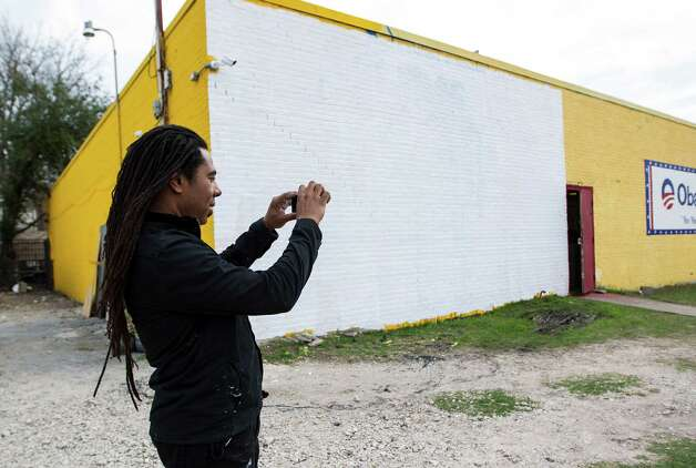 Artist Reginald Adams takes a photo in front of the white washed wall which formerly was his mural of Barack Obama on one of the The Breakfast Klub building at the corner of Travis and Alabama, Monday, Jan. 28, 2013, in Houston. Overnight, vandals threw paint on the Barack Obama mural, defacing it. Adams got a text about 7am this morning and immediately white washed the wall.  Plans are for another mural to go up in the next few weeks.  ( Karen Warren / Houston Chronicle ) Photo: Karen Warren, Staff / © 2013 Houston Chronicle