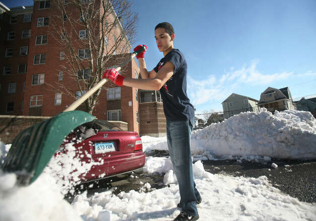 Christian Centano, 16, shovels out a car in the parking lot at the Charles F. Greene Homes housing project in Bridgeport, Conn. on Wednesday, February 13, 2013. Residents are frustrated about the lack of snow removal at both the complex and adjacent Highland Avenue. Photo: Brian A. Pounds / Connecticut Post