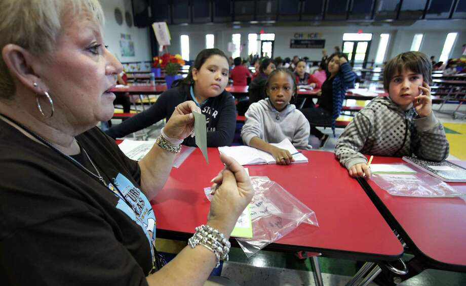 Reading specialist Amy Owens explains a math station to students preparing for the STAAR. The  system has become an arbitrary, high-stakes and often punitive obstacle to graduation for some students and a hindrance to educators. Photo: Bob Owen, San Antonio Express-News