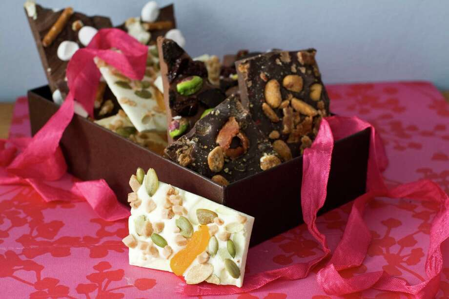 In this image taken on Jan. 21, 2013, four variations of Valentine's Day chocolate bark are shown in Concord, N.H. You can top the chocolate with whatever your love loves.(AP Photo/Matthew Mead) Photo: Matthew Mead