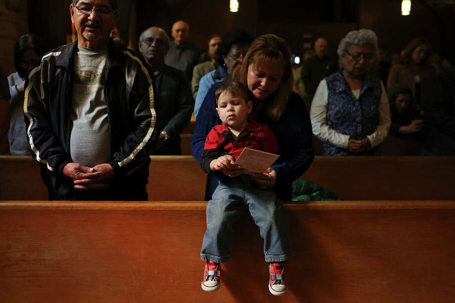 Mary Corella, center, with her husband, Pete Corella, left, holds their grandson, Mason Castillo, 23 months, during the Ash Wednesday service at St. Benedict Catholic Church in San Antonio on Wednesday, Feb. 13, 2013. Photo: Lisa Krantz, San Antonio Express-News / © 2012 San Antonio Express-News