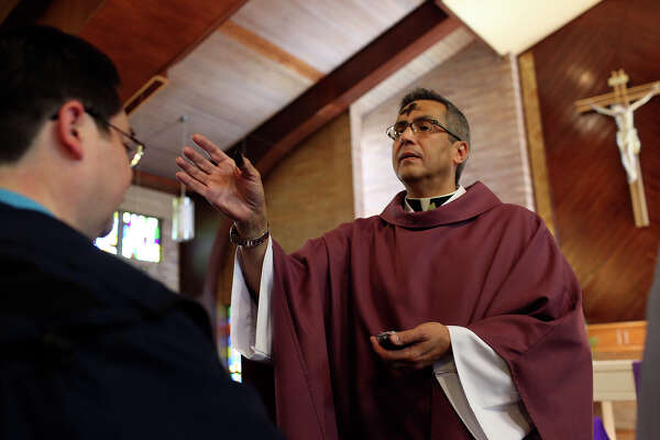 Father Eddie Bernal imposes ashes on the foreheads of worshippers  during the Ash Wednesday service at St. Benedict Catholic Church in San Antonio on Wednesday, Feb. 13, 2013.