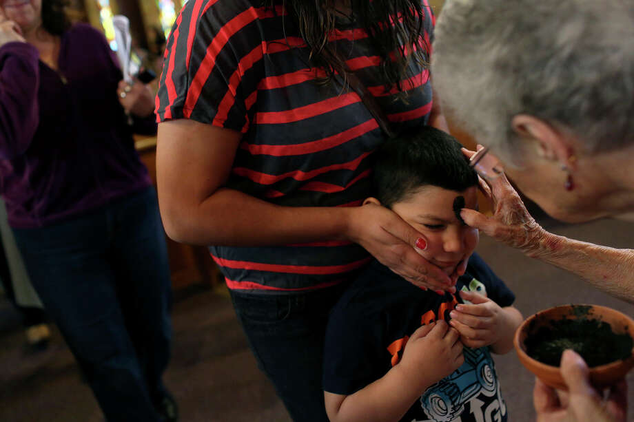 Cristian Arellano, 3, held by his mother, Maria Arellano, 3, receives ashes during the Ash Wednesday service at St. Benedict Catholic Church in San Antonio on Wednesday, Feb. 13, 2013. Photo: Lisa Krantz, San Antonio Express-News / © 2012 San Antonio Express-News