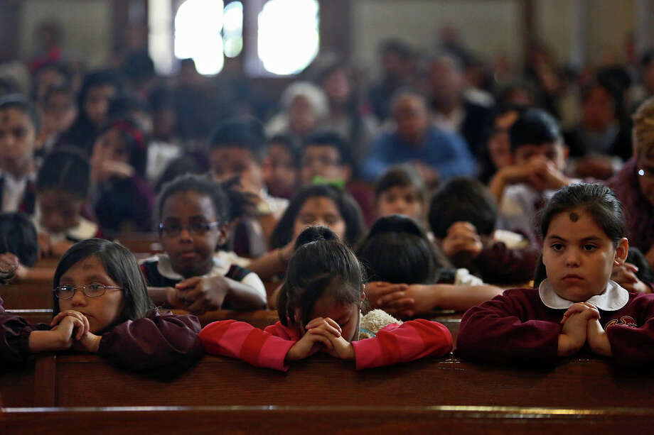 Second graders including Judea Favella, 7, from left, Iliana Galan, 7, and Briana Rodriguez, 7, attend the Ash Wednesday mass with fellow students from the Little Flower Catholic School at the Basilica of the National Shrine of the Little Flower in San Antonio on Wednesday, Feb. 13, 2013. Photo: Lisa Krantz, San Antonio Express-News / © 2012 San Antonio Express-News