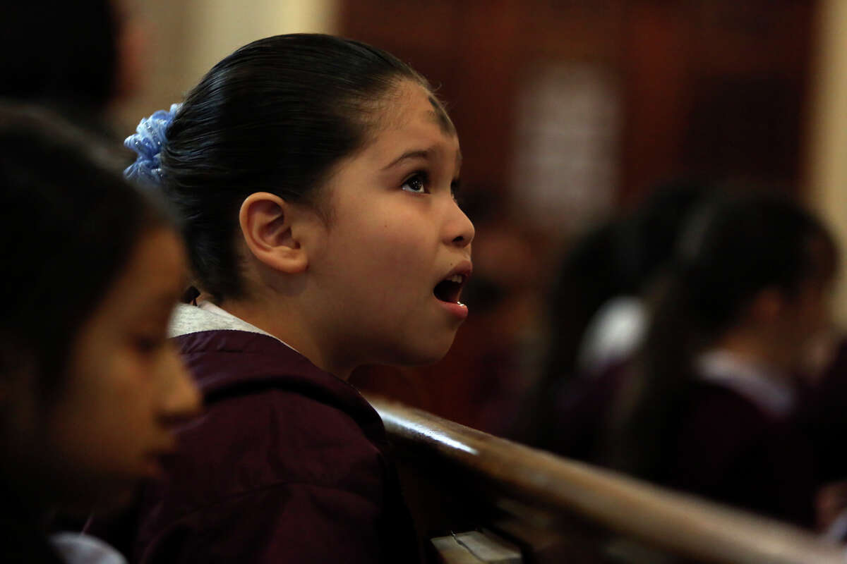 Savannah Suarez, 6, a first grader at Little Flower Catholic School, sings with fellow students during the Ash Wednesday Mass at the Basilica of the National Shrine of the Little Flower in San Antonio on Wednesday, Feb. 13, 2013.