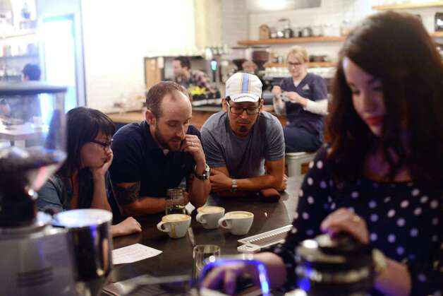 Skylar Altman (from left), Adam Biechlin and Rafael Mancilla judge lattes as Paige Arbogast works on her entry during the Latte Art Throwdown. Photo: Billy Calzada, San Antonio Express-News / San Antonio Express-News
