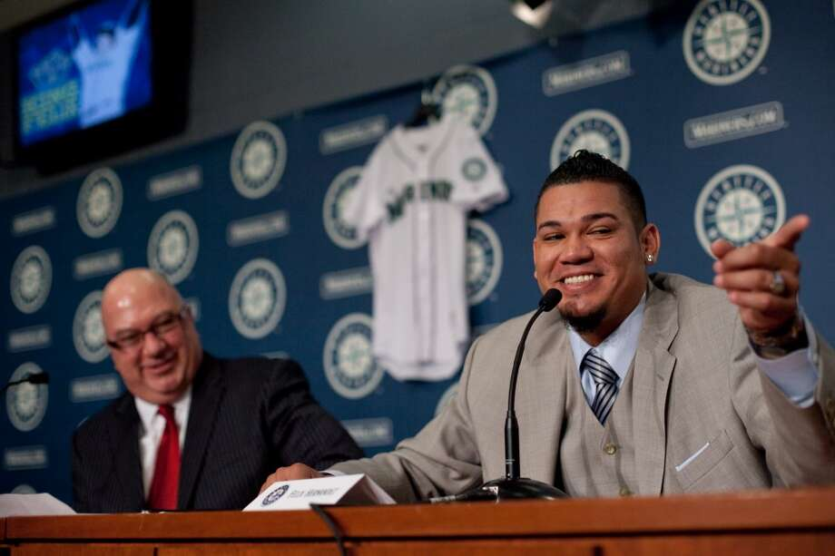 Seattle Mariners pitcher Felix Hernandez points toward his family as he signs a 7 year deal with Mariners General Manger Jack Zduriencik on Wednesday, February 13, 2013 at Safeco Field in Seattle.