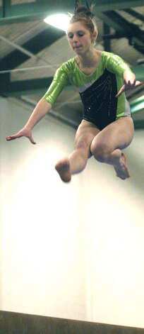 Taylor Fish of the Green Wave soars above the balance beam during a New Milford High School gymnastics meet vs. Oxford and Newtown at NMHS, Jan. 25, 2013 Photo: Norm Cummings