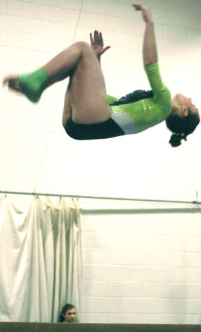 Alison Profeta of the Green Wave engages in a challenging routine on balance beam during a New Milford High School gymnastics meet vs. Oxford and Newtown at NMHS, Jan. 25, 2013 Photo: Norm Cummings