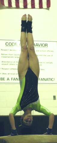 Green Wave frosh Kalee Oelgoetz offers a glimpse of her vaulting skills for New Miford High School gymnastics during the South-West Conference championship meet at NMHS, Feb. 7,,2013  for New Miford High School gymnastics during the South-West Conference championship meet at NMHS, Feb. 7,,2013 Photo: Norm Cummings