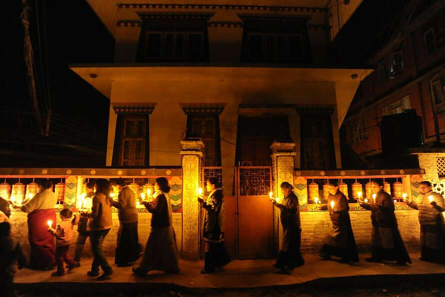 Left: Tibetans in Nepal hold a candlelight vigil after the self-immolation attempt to protest Chines