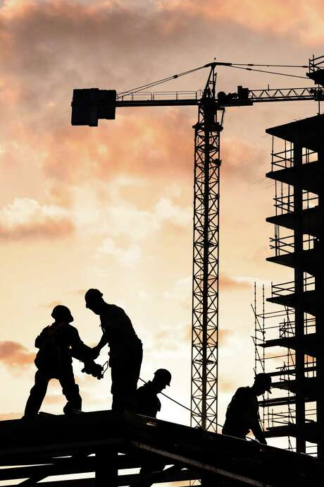 construction workers, orangey sky, crane in background FOTOLIA / sculpies - Fotolia