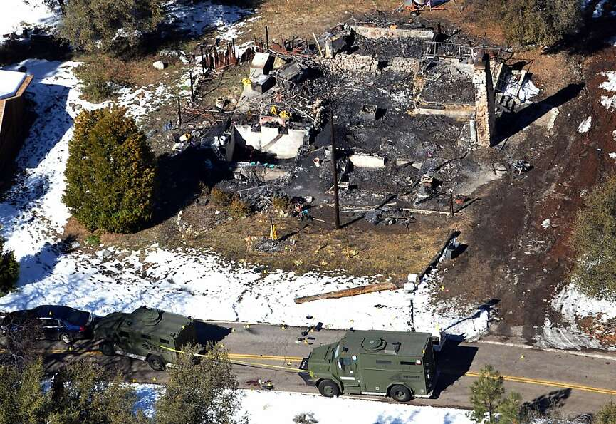 Law enforcement authorities investigate the burned-out cabin where murder suspect Christopher Dorner