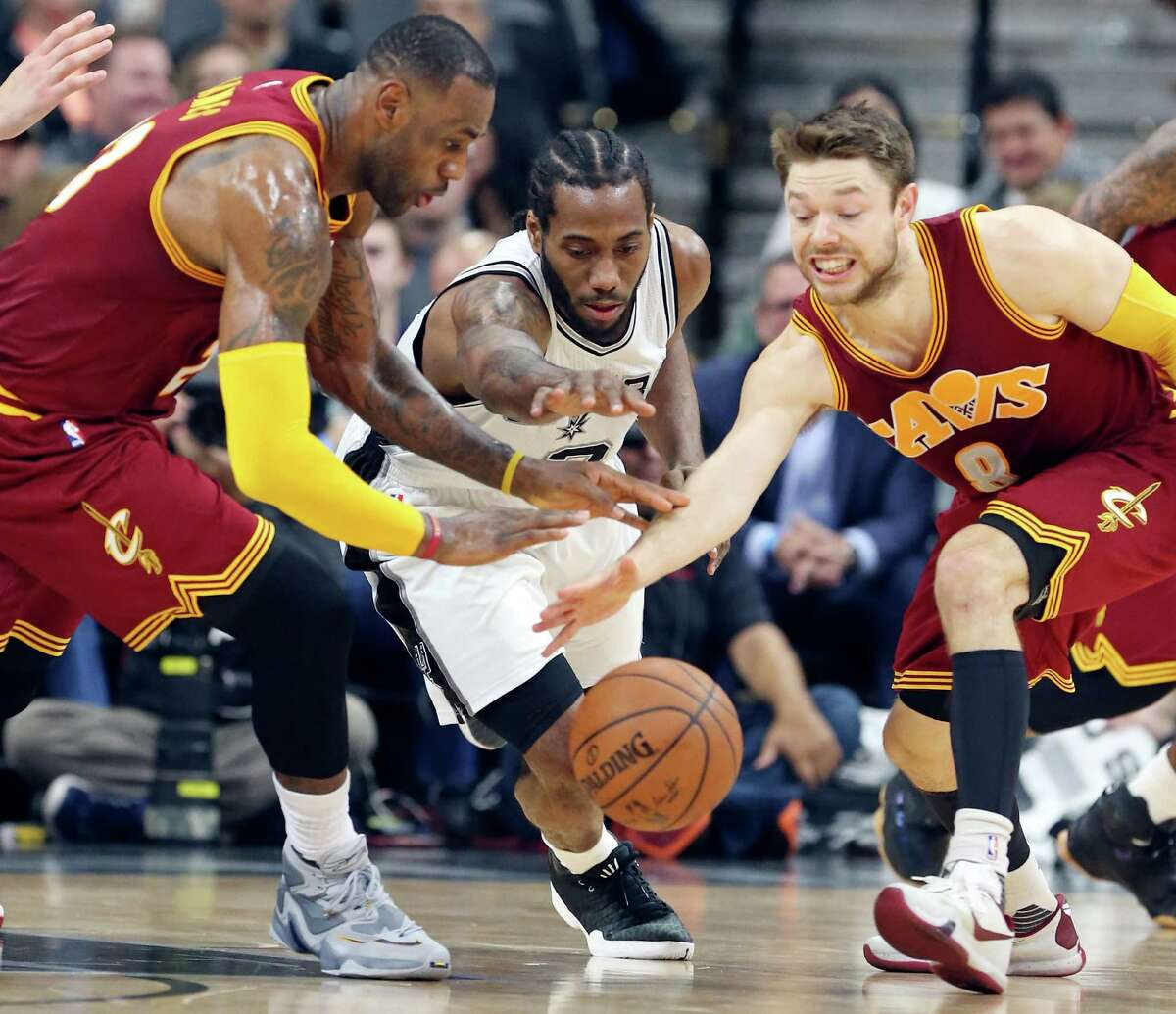 Cleveland Cavaliers' LeBron James (from left), San Antonio Spurs' Kawhi Leonard, and Cleveland Cavaliers' Matthew Dellavedova grab for a loose ball during first half action Thursday Jan. 14, 2016 at the AT&T Center.