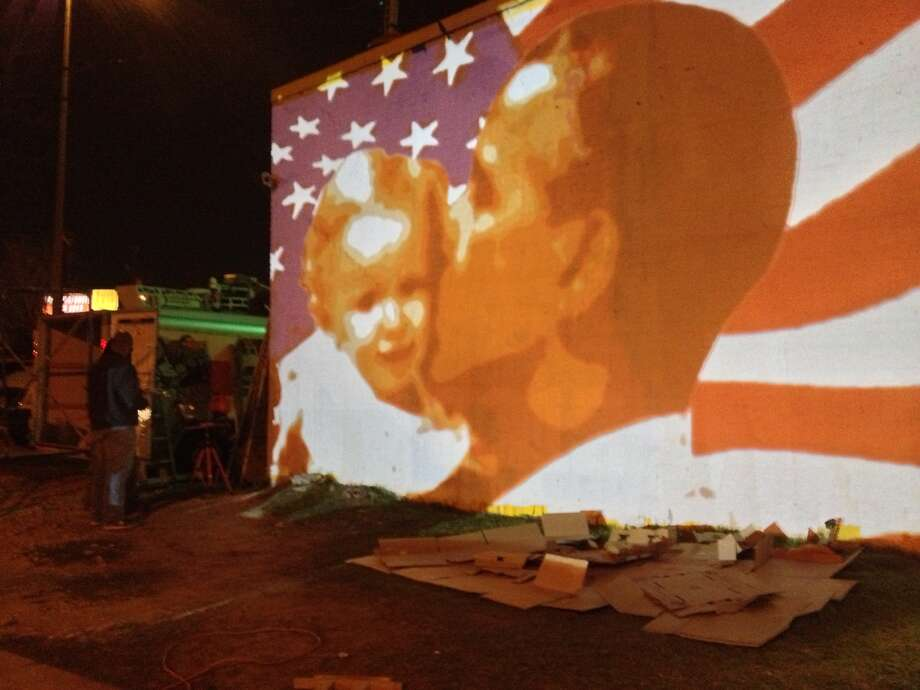 Participants help paint a newly redesigned mural of President Obama across the street from The Breakfast Klub restaurant in Midtown. The mural's artist used a projector so volunteers can help trace the image. (Photo by Erin Mulvaney/Chronicle)
