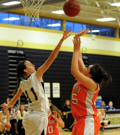 Trumbull's #11 Rachel Carron, left, defends the hoop as Danbury's #25 Kayla Handberry attempts a shot, during girls basketball action in Trumbull, Conn. on Wednesday February 13, 2013. Photo: Christian Abraham / Connecticut Post