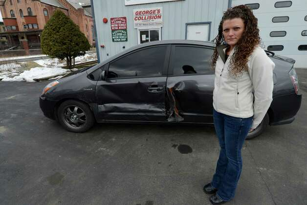 Samara Ceccucci stands with her damaged Toyota Prius, which was hit by a Troy police cruiser in April. (Skip Dickstein/Times Union) Photo: SKIP DICKSTEIN / 00021146A