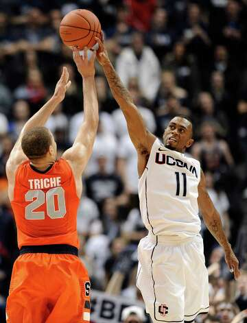 Connecticut's Ryan Boatright, right, blocks a shot-attempt by Syracuse's Brandon Triche in the final minutes of second half of an NCAA college basketball game in Hartford, Conn., Wednesday, Feb. 13, 2013. Connecticut won 66-58. (AP Photo/Jessica Hill) Photo: Jessica Hill, Associated Press / FR125654 AP