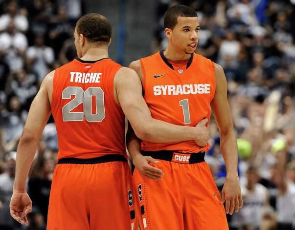 Syracuse's Brandon Triche (20) holds back teammate Michael Carter-Williams (1) after Carter-Williams reacted to receiving his fourth foul during the second half of an NCAA college basketball game against Connecticut in Hartford, Conn., Wednesday, Feb. 13, 2013. Connecticut won 66-58. (AP Photo/Jessica Hill) Photo: Jessica Hill, Associated Press / FR125654 AP