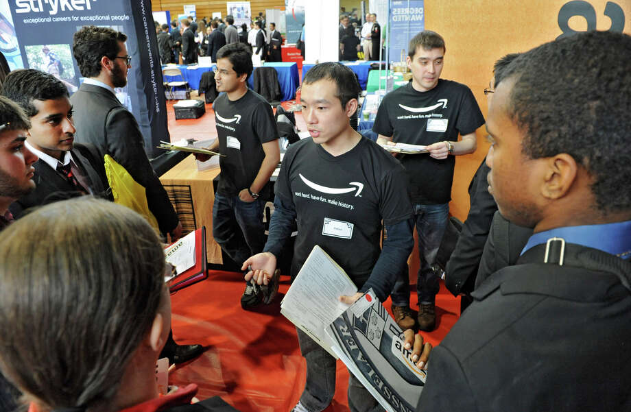 Amazon representative Julian Lai, center, accepts resumes and talks to students during the annual Spring Career Fair at Rensselaer Polytechnic Institute on Wednesday Feb. 13, 2013 in Troy, N.Y. The event, hosted by the Center for Career and Professional Development (CCPD) had more than 300 representatives from more than 117 public and private-sector employers. (Lori Van Buren / Times Union) Photo: Lori Van Buren