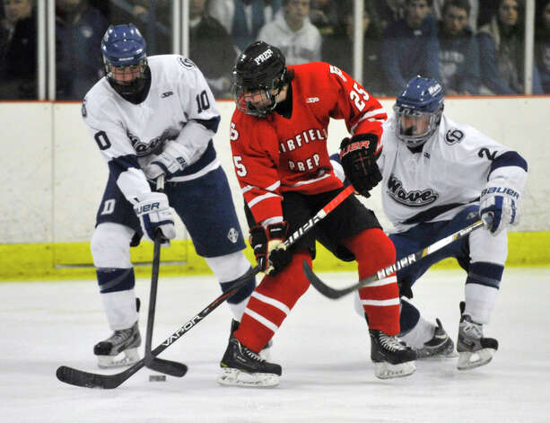 Darien's Jack Massie, left, and Nicholas Allam fight Fairfield Prep's Michael Ventricelli for control of the puck during their game at Darien Ice Rink on Wednesday, Feb. 13, 2013. Fairfield Prep won, 6-0. Photo: Jason Rearick / The News-Times