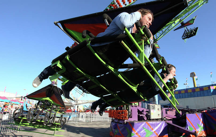 "Rob Baird (left) and Rick Brantley take a ride on ""Cliff Hanger""  - one of several thrill rides - at the 2013 San Antonio Stock Show and Rodeo on Wednesday, Feb. 13, 2013. Photo: Kin Man Hui, San Antonio Express-News / © 2012 San Antonio Express-News"