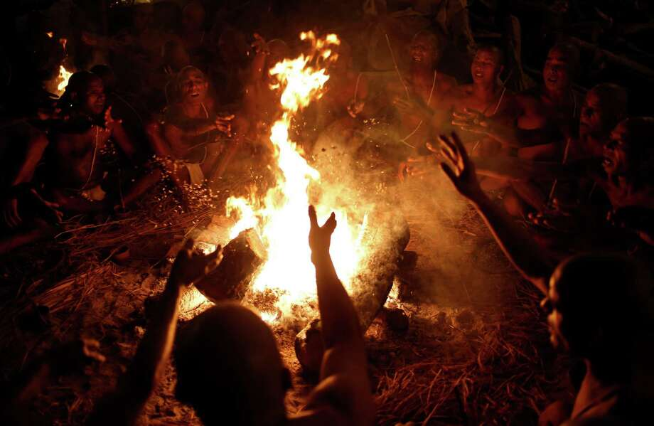 Hindu holy men make offerings to the fire as they chant mantras to be initiated as 'Naga sadhus' or naked Hindu holy men at the Maha Kumbh festival in Allahabad, India, Wednesday, Feb. 13, 2013. The significance of nakedness is that one will not have any worldly ties to material belongings, even something as simple as clothes. Rituals that transform selected holy men to Naga can only be done at the Kumbh festival. Photo: Saurabh Das, Associated Press / AP