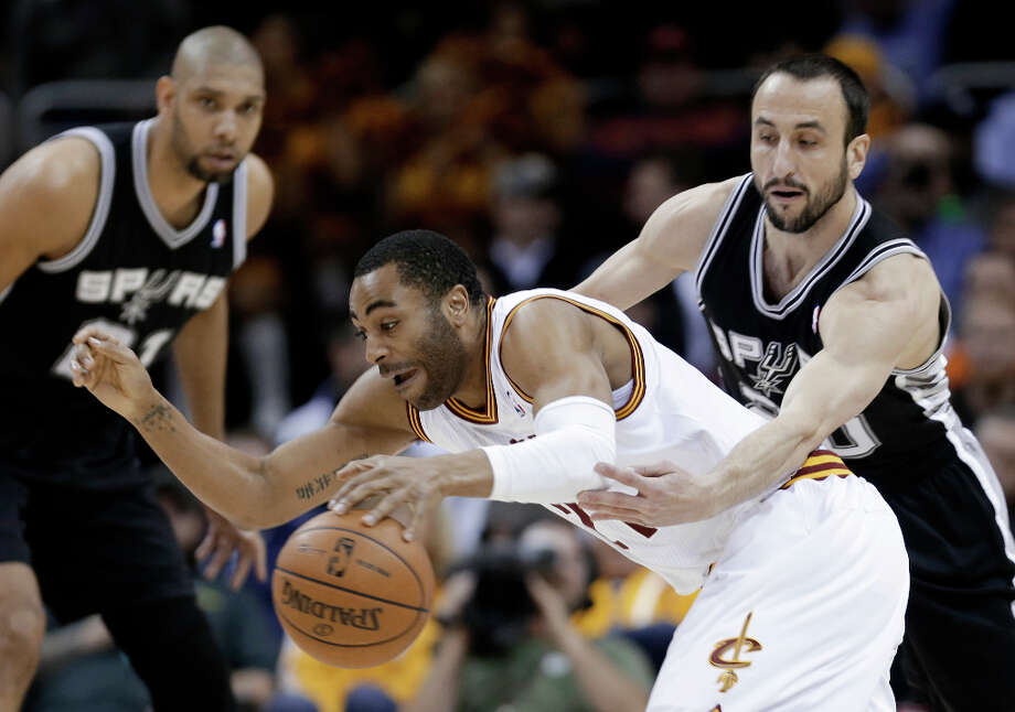 San Antonio Spurs' Manu Ginobili, right, tries to knock the ball loose from Cleveland Cavaliers' Wayne Ellington during the first quarter of an NBA basketball game Wednesday, Feb. 13, 2013, in Cleveland. Photo: Tony Dejak, Associated Press / AP