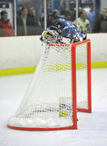 The Darien boys left their helmets on top of the goal during the singing of the National Anthem before their game against Fairfield Prep at Darien Ice Rink on Wednesday, Feb. 13, 2013. Photo: Jason Rearick / The News-Times