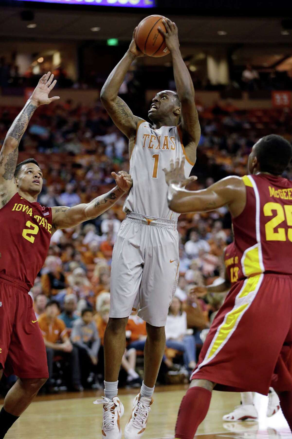 Texas' Sheldon McClellan (1) shoots over Iowa State's Chris Babb (2) and Tyrus McGee (25) during the first half of an NCAA college basketball game, Wednesday, Feb. 13, 2013, in Austin, Texas. (AP Photo/Eric Gay)